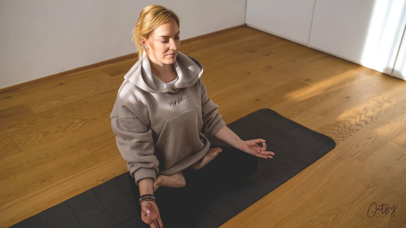 Polona, ki med meditacijo sedi na tleh po turško