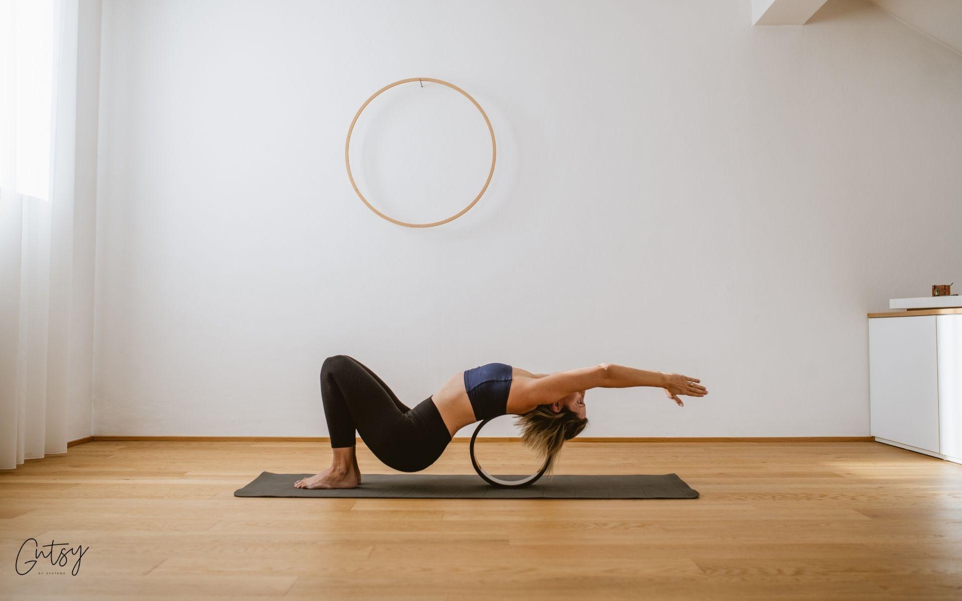 Aleksandra med prakso joge v zaklonu na joga kolesu