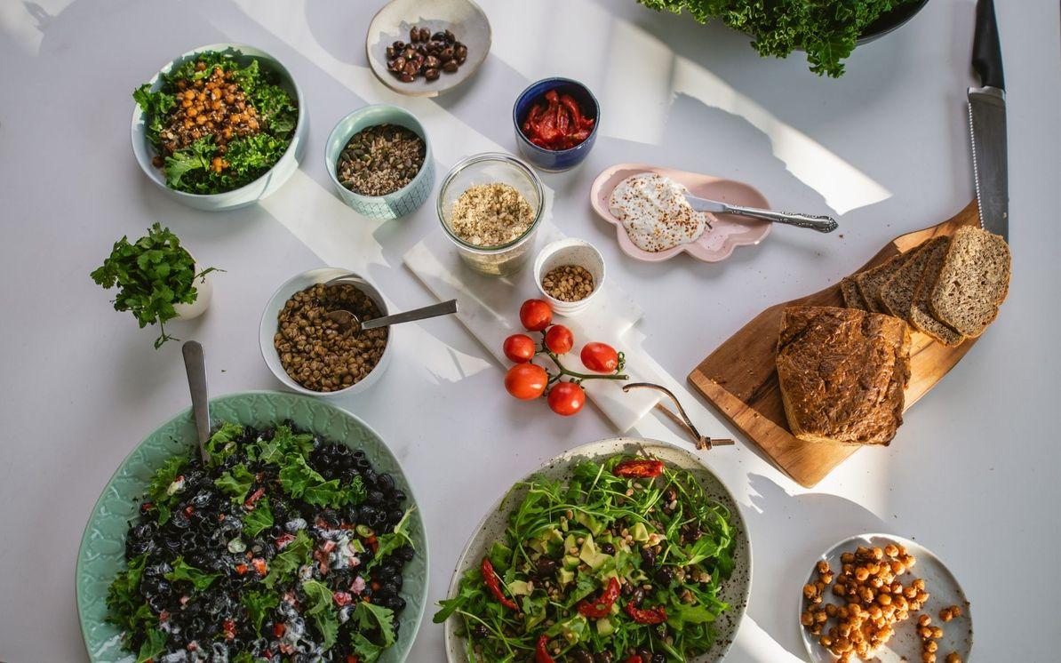 razna zelenjava, stročnice, kruh in drugi dodatki za kreiranje uravnoteženega obroka na beli podlagi